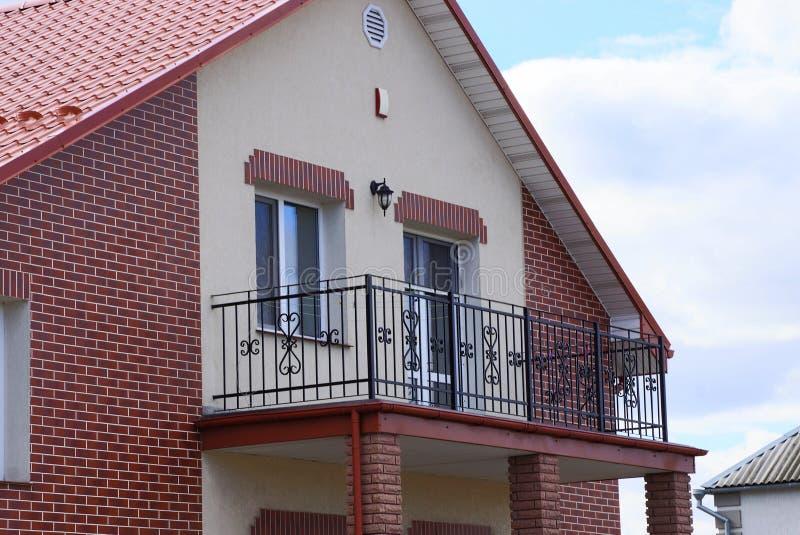 Svart öppen järnbalkong på fasaden av ett brunt tegelstenhus med ett fönster och en dörr royaltyfri foto
