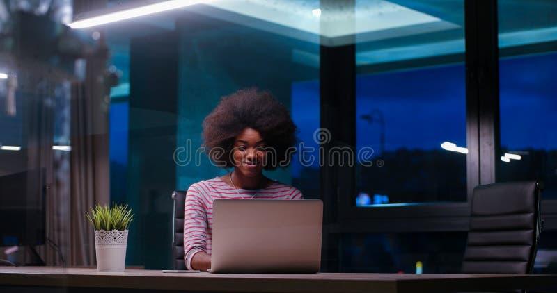 Svart affärskvinna som använder en bärbar dator i nattstartkontor fotografering för bildbyråer
