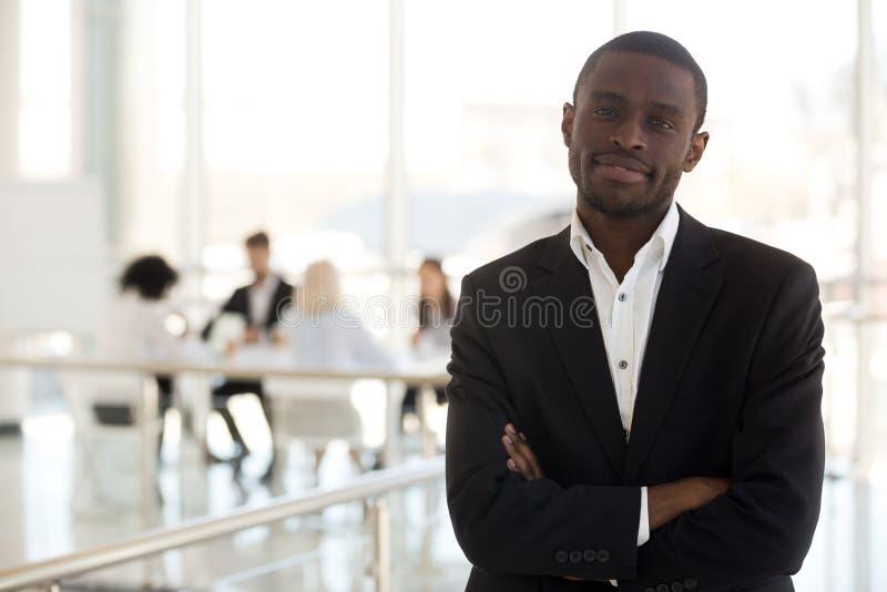Svart affärsman som i regeringsställning står med händer som korsas på bröstkorg royaltyfri foto