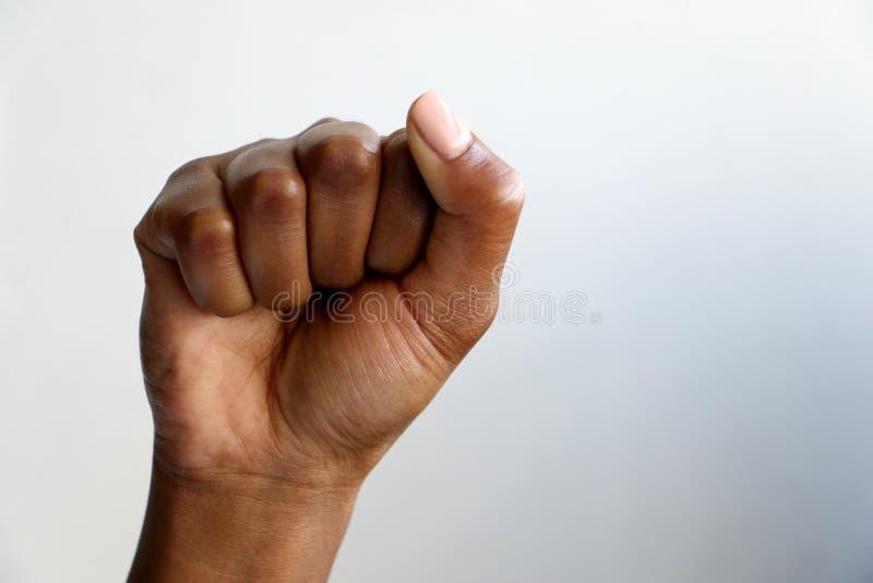 Svart afrikansk kvinnlig hand f?r indier som gripas h?rt om i en n?ve, svart makt fotografering för bildbyråer