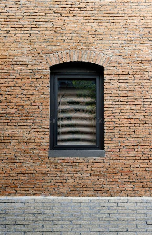 Svart aluminiumfönsterram i den byggande väggen som göras av röd tegelsten royaltyfria bilder