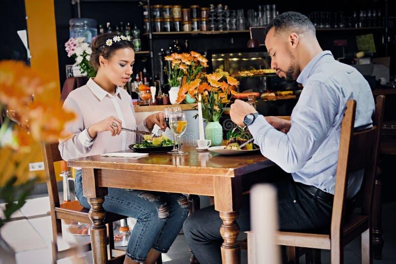 Svart amerikansk man och kvinnlig som äter strikt vegetarianmat arkivfoto