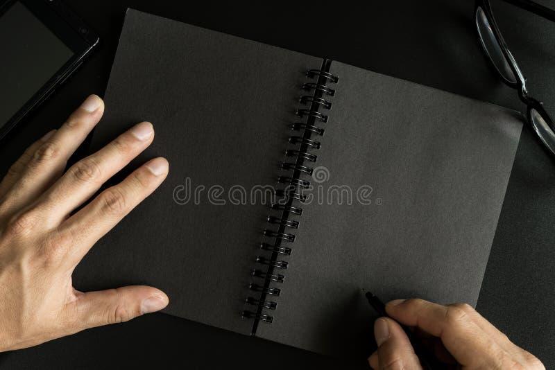 Svart anteckningsbok med kopieringsutrymme med handhandstil royaltyfria bilder