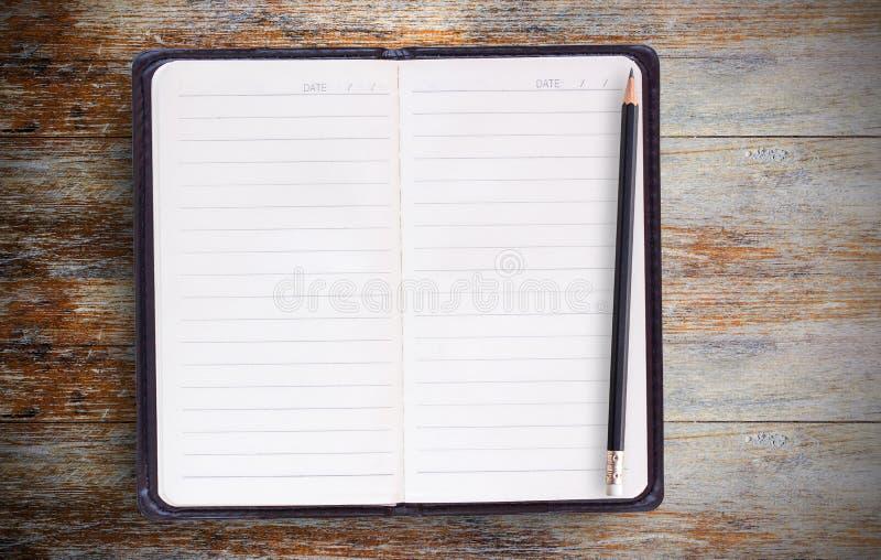 Svart anteckningsbok på träkontorsskrivbordet, bästa sikt royaltyfria foton