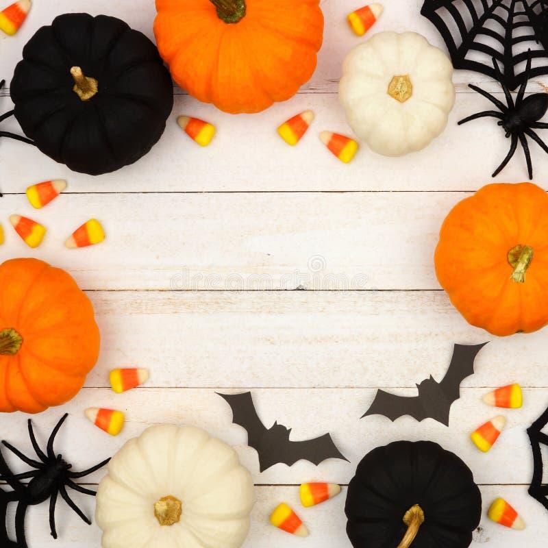 Svart-, apelsin- och vitallhelgonaaftonram över vitt trä arkivfoton