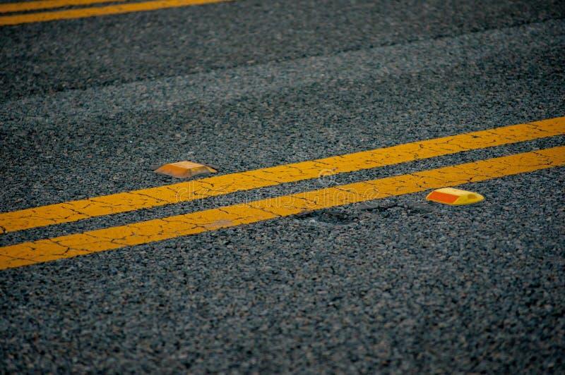 Svart asfaltväg med gula linjer och orange reflektorer royaltyfri bild
