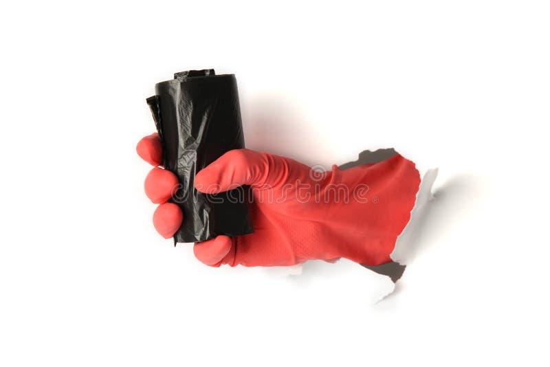 Svart avfallpåse i hand i skyddande handske på vit bakgrund fotografering för bildbyråer