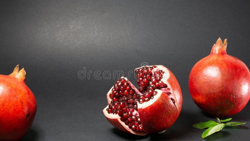 Svart bakgrund, i fotoet där är frukt för tre granatäpplen i mitt av rosenträt, och granatäpplekorn är synliga arkivfoton