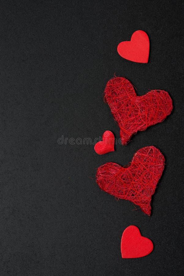 Svart bakgrund med olika röda hjärtor royaltyfri foto