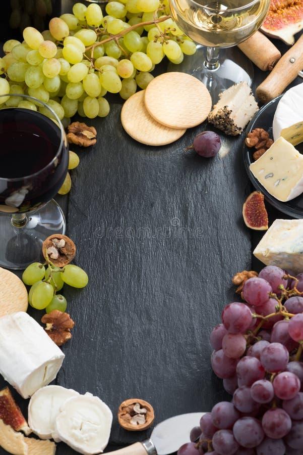 Svart bakgrund med ostar, druvor, smällare och vin arkivbilder