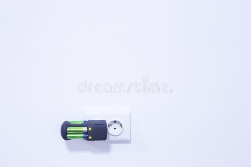 Svart batteriuppladdare aa på vit bakgrund arkivfoton
