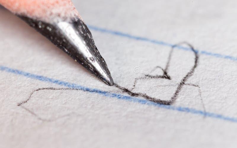 Svart blyertspenna på papper Makro arkivfoto