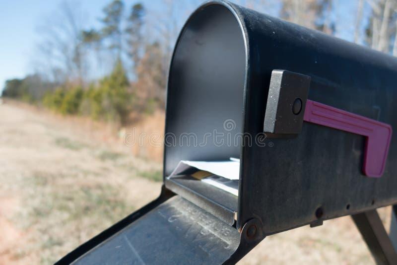 Svart brevlåda och stolpe - kontorspost med blå himmel arkivfoto