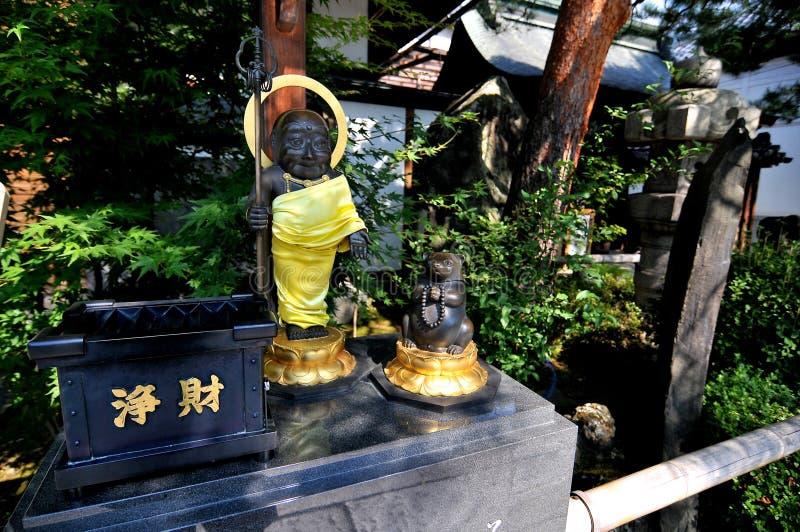Svart Buddha och be tvättbjörnstatyn på ingången av den Zenko-ji templet i Japan royaltyfria foton