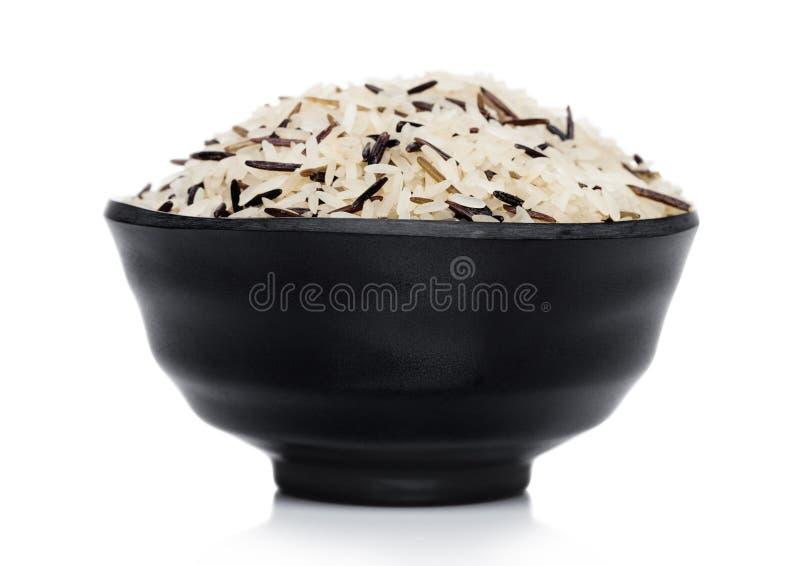Svart bunke av r?tt organiskt basmati l?ngt korn och l?sa ris p? vit bakgrund sund mat royaltyfria foton