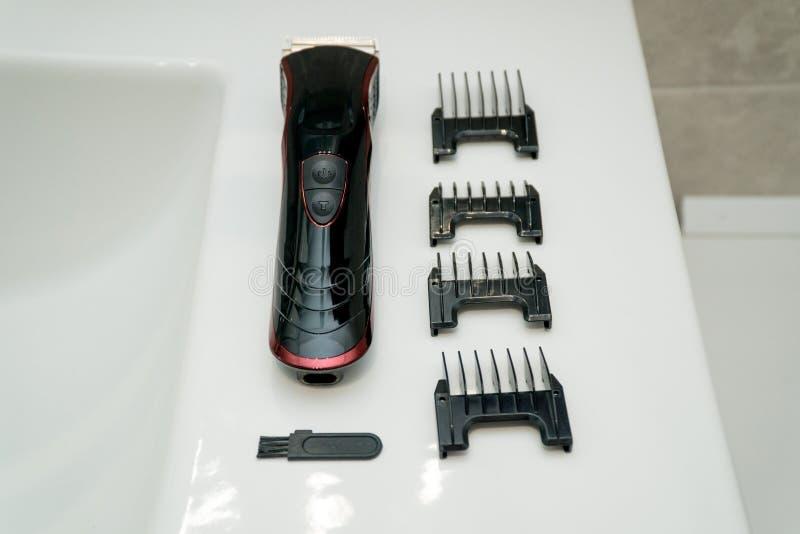 Svart clipper i ett badrum Den unga asiatiska flickan som kammar h?r med, fingrar isolerat p? vitbakgrund arkivfoto