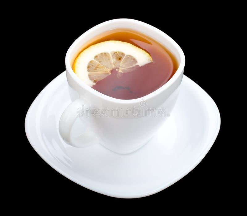 svart cuppacitronsaucer arkivfoto