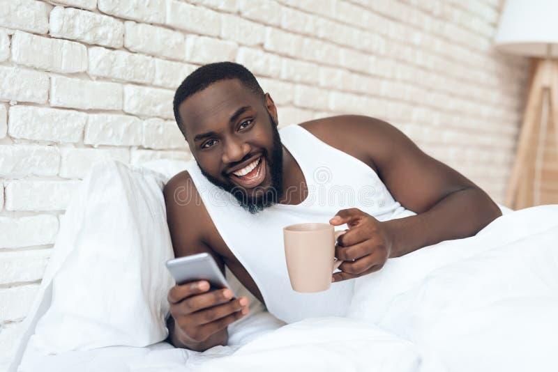 Svart den väckte mannen dricker kaffe, i att bläddra för säng arkivbild