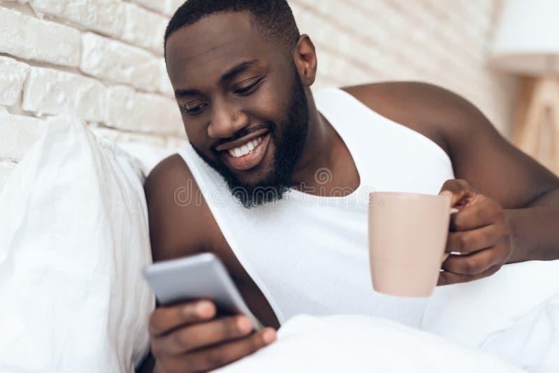 Svart den väckte mannen dricker kaffe, i att bläddra för säng royaltyfri fotografi