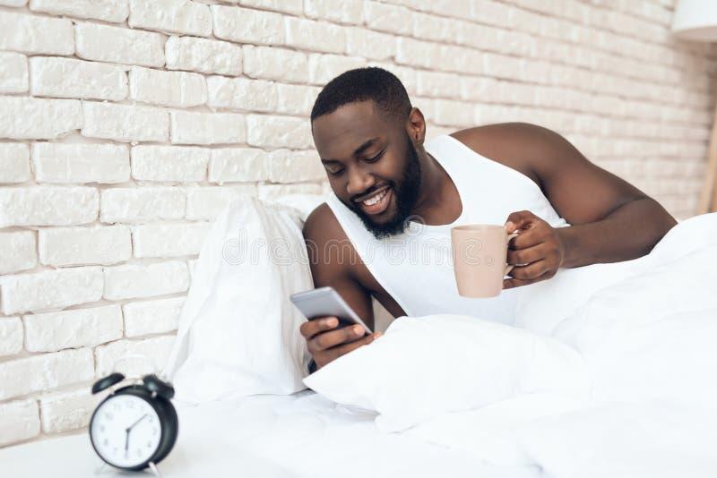 Svart den väckte mannen dricker kaffe, i att bläddra för säng arkivfoto