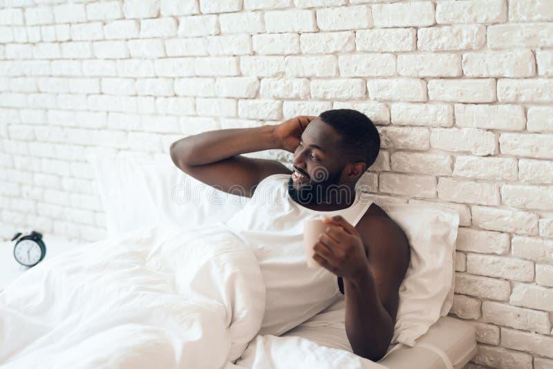 Svart den väckte mannen dricker kaffe i säng royaltyfri bild