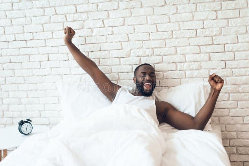 Svart den väckte mannen sträcks ut i säng royaltyfria bilder