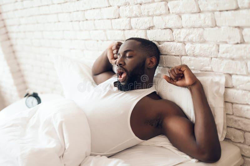 Svart den väckte mannen sträcks ut i säng arkivbild