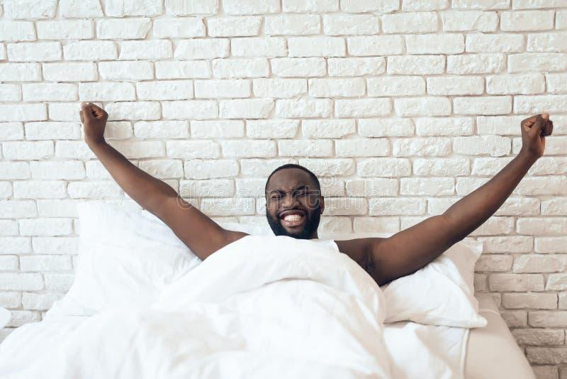 Svart den väckte mannen sträcks ut i säng royaltyfri fotografi