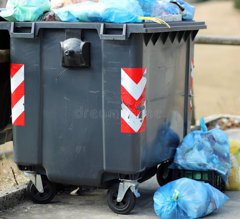 svart dumpster och många avskrädepåsar royaltyfria foton
