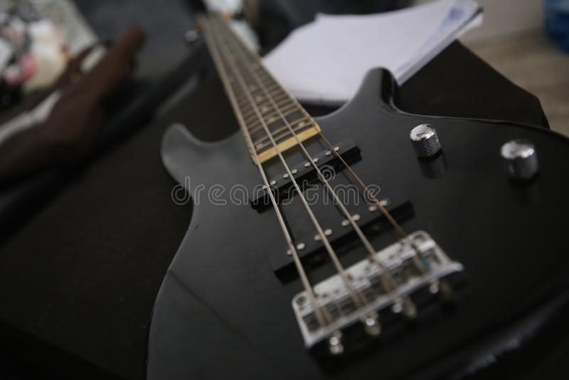 Svart electro gitarr med justerbart och fyra rader arkivfoton