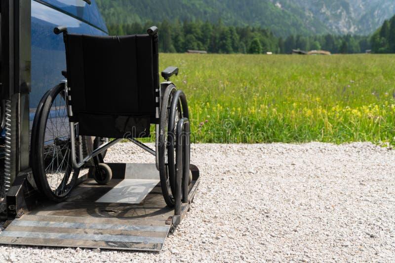 Svart elektrisk elevator specialiserat medel för folk med handikapp Tom rullstol på en ramp med naturen och arkivbilder