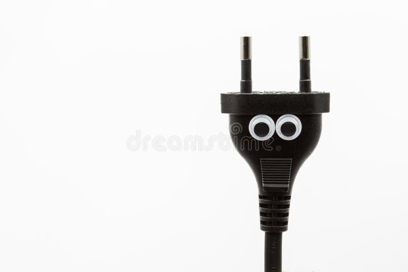 Svart elektrisk propp med googly ögon på vit bakgrund - nära övre arkivfoton