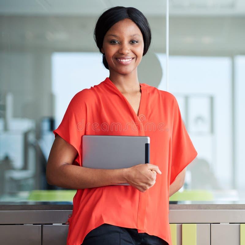 Svart entreprenör som ler på kameran, medan stå i affärsvardagsrum royaltyfri foto