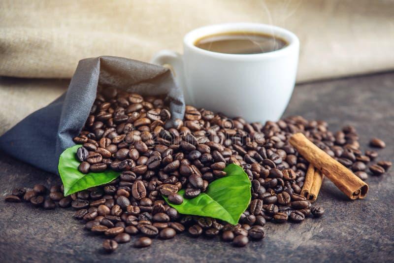 Svart espressokopp för vit med en hög av kaffebönor och gräsplansidor i påse på vit linnebakgrund arkivbild