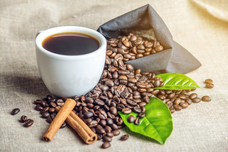 Svart espressokopp för vit med en hög av kaffebönor och gräsplansidor i påse på vit linnebakgrund royaltyfria bilder