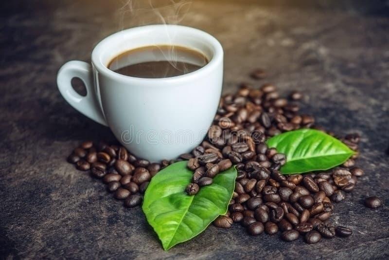 Svart espressokopp för vit med högen av kaffebönor och gräsplansidor i påse på mörk bakgrund arkivfoton