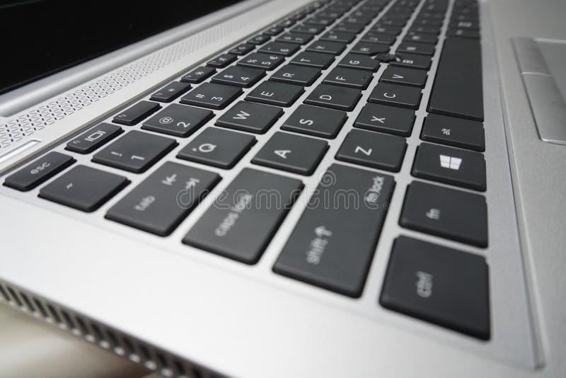 Svart försilvrar bärbar datortangentbordet med vita bokstäver moderna apparater som skriver hjälpmedlet, trycktext arkivfoton