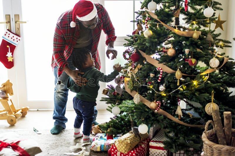 Svart familj som tycker om julferie arkivfoton