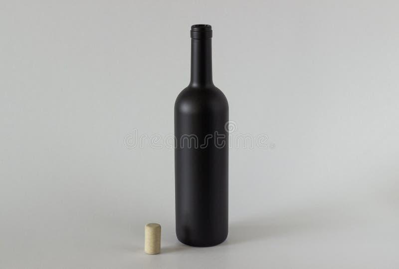 Svart flaska och propp på en vit bakgrund fotografering för bildbyråer