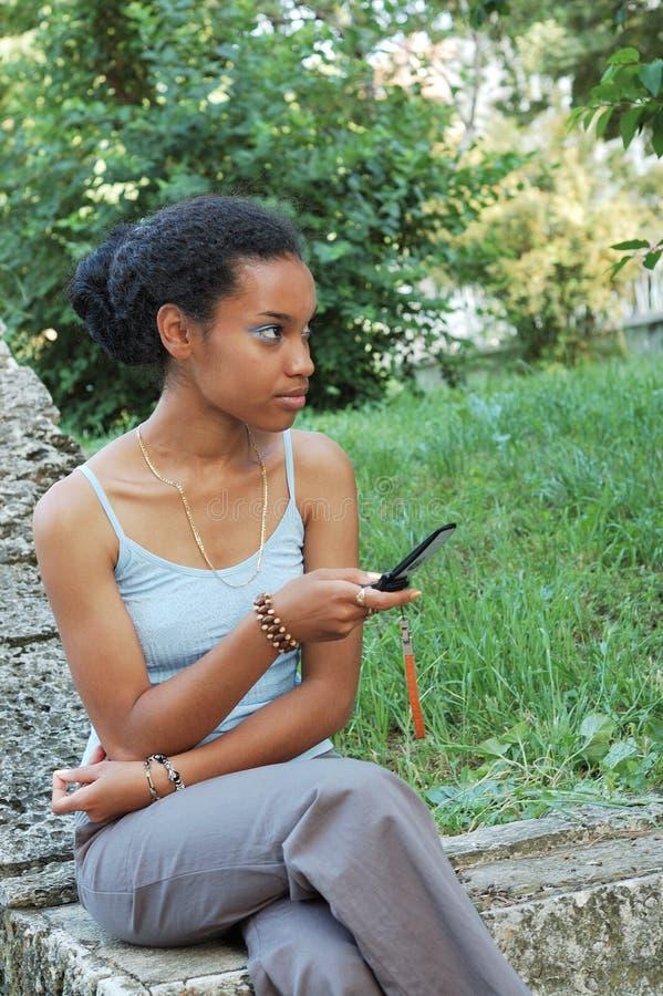 Svart flicka med den mobila telefonen royaltyfria foton