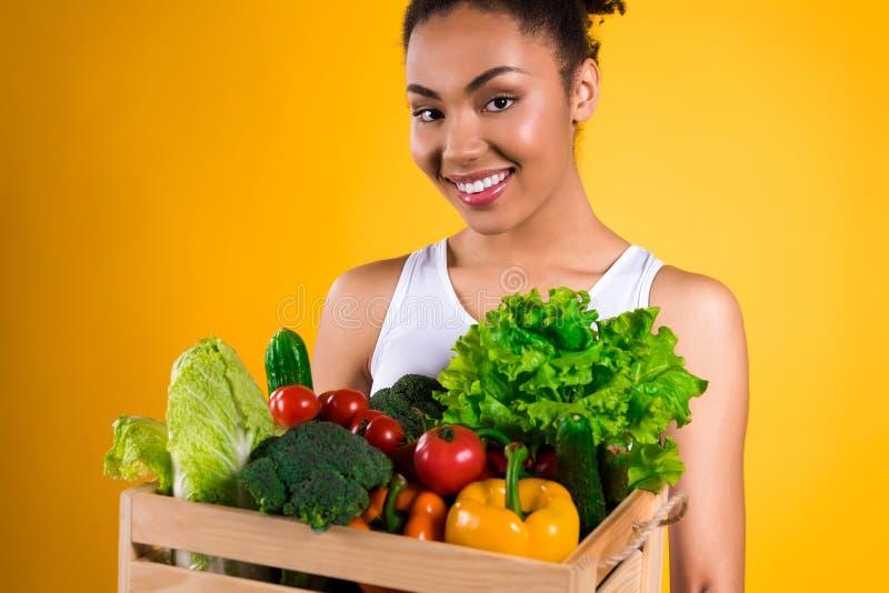 Svart flicka med spjällådan av isolerade grönsaker royaltyfria foton
