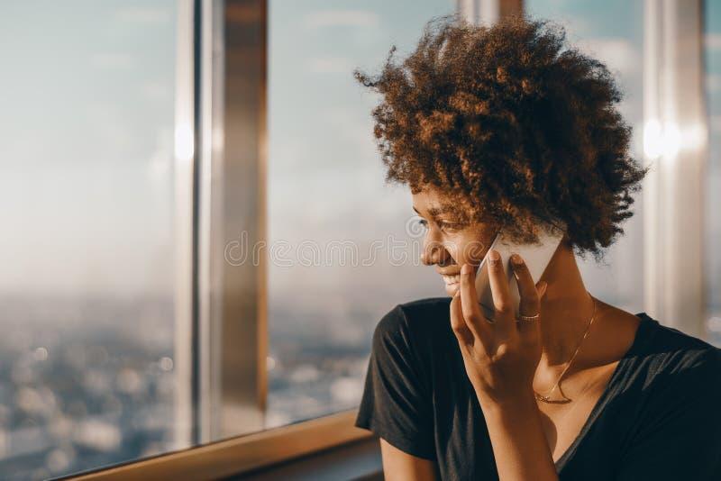 Svart flicka nära fönstret av skyskrapan som talar på mobiltelefonen arkivbild