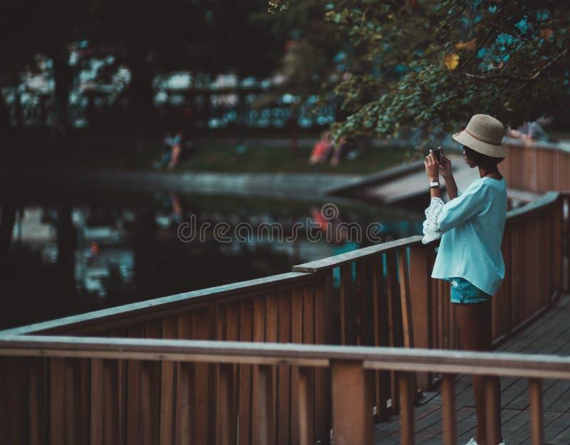 Svart flicka som fotograferar dammet genom att använda hennes mobiltelefon fotografering för bildbyråer