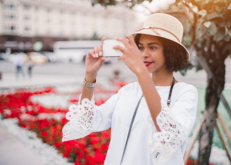 Svart flicka som fotograferar utomhus på hennes mobiltelefon royaltyfri fotografi