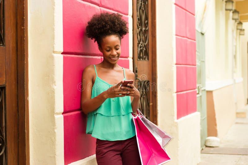 Svart flickashopping och textMessaging på telefonen arkivfoto