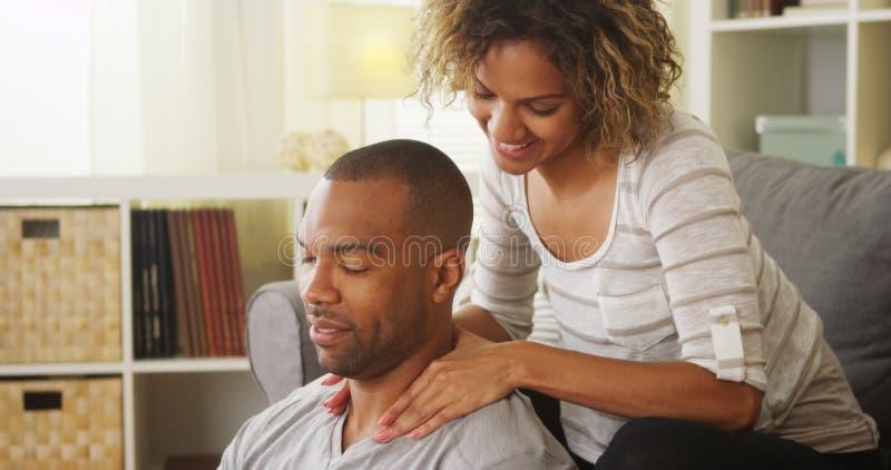 Svart flickvän som ger pojkvänmassage arkivbild