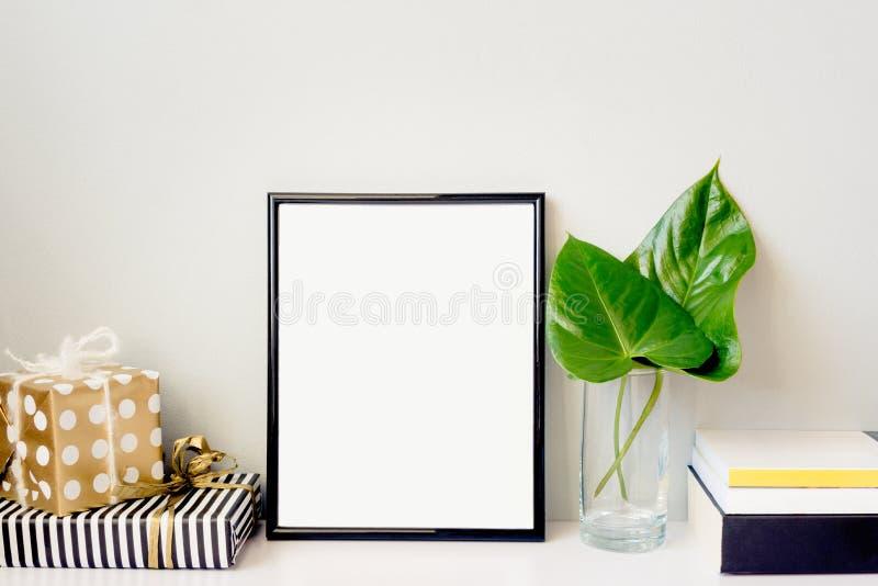 Svart fotoram, grön växt i en crystal vas, gåvaaskar och en hög av böcker som är ordnade mot den tomma gråa väggen Rammodell royaltyfri bild