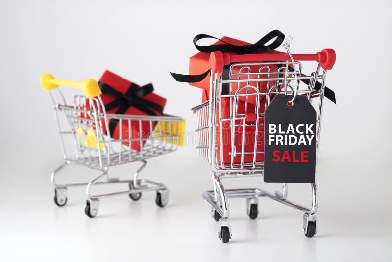 Svart fredag etikett med den röda gåvaasken i shoppingvagn royaltyfria bilder