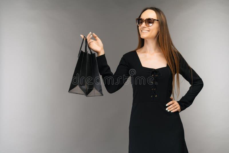 Svart fredag f?rs?ljningsbegrepp Shoppa kvinnainnehavpåsen som isoleras på bakgrund i ferie arkivbilder