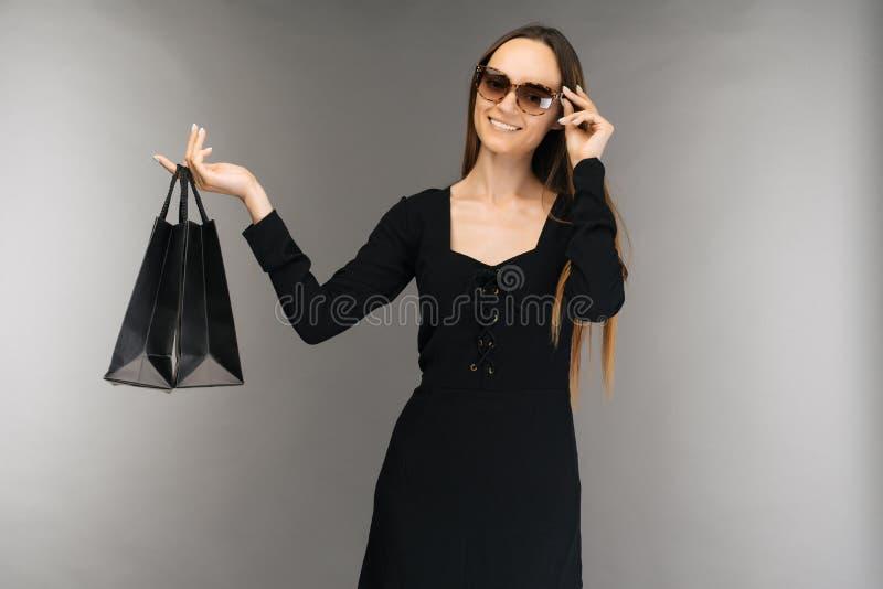 Svart fredag f?rs?ljningsbegrepp Shoppa kvinnainnehavpåsen som isoleras på bakgrund i ferie arkivbild